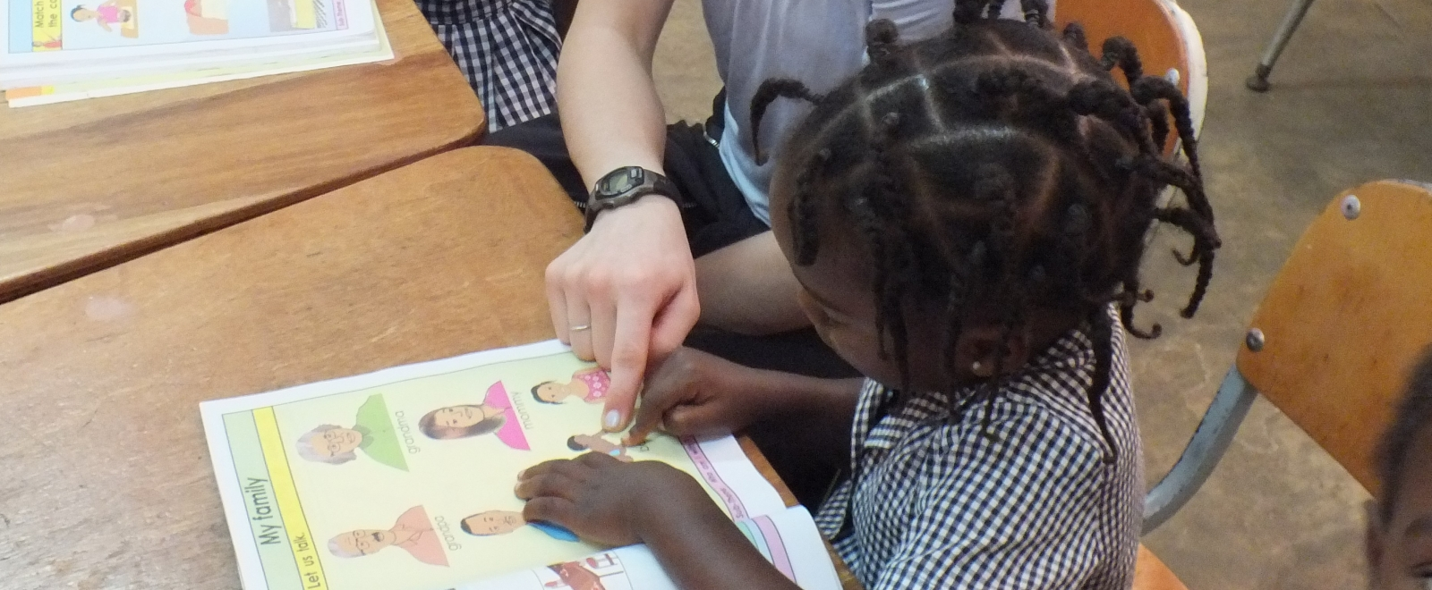 A volunteer works with children on English lessons in Jamaica with a group.